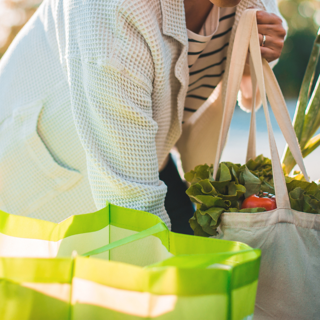A woman picks up her grocery bags.